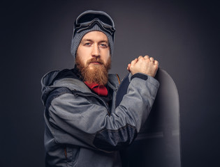 Brutal redhead snowboarder with a full beard in a winter hat and protective glasses dressed in a snowboarding coat posing with snowboard at a studio, looking away. Isolated on the gray background.