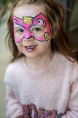 Pretty excited cute young girl with face painting like a butterfly