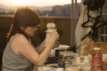 pottery woman decorating a piece in her studio