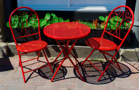 Red cafe and chairs on the sidewalk.