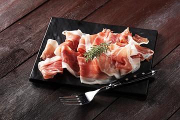 Italian prosciutto crudo or jamon with rosemary. Raw ham