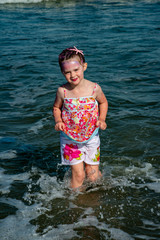 Portrait of a beautiful young mermaid girl playing in the ocean surf at the beach on a sunny day