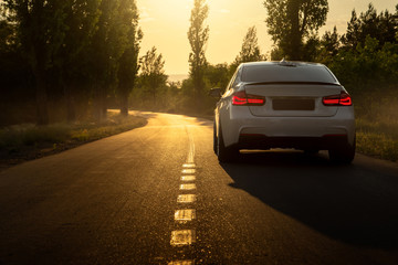 Wall Mural - White car is parked on empty countryside asphalt road at sunset