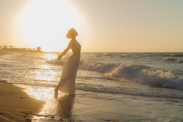 Woman with arms raised up, barefoot, feeling happy, alive and free in nature meditating at sandy misty beach breathing clean fresh ocean air at dusk. Summer holidays lifestyle concept