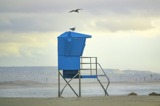 Blue Lifeguard stand (on duty) on beach in sunset lights. Blurred Clouds on background.