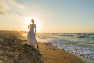 Woman in white dress, barefoot, feeling happy, alive and free in nature meditating at sandy misty beach breathing clean fresh ocean air at dusk. Summer holidays lifestyle concept