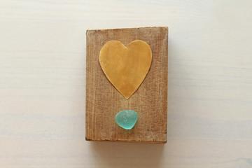 Golden heart on a wooden background of natural wood black American walnut. Beautiful romantic wallpaper. Gold heart