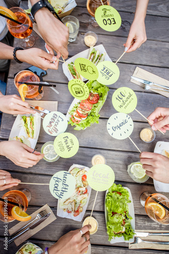 People holding plates with healthy food slogans on the table