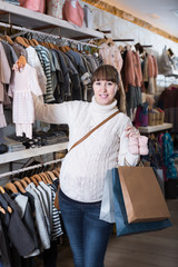 Happy pregnant woman choosing clothes for baby