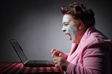femme ronde drôle en peignoir et bigoudis devant son ordinateur portable