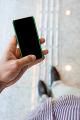 Close up of mobile phone with corporate environment blurred in the background.