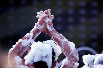 raised hands of a man in a foam disco