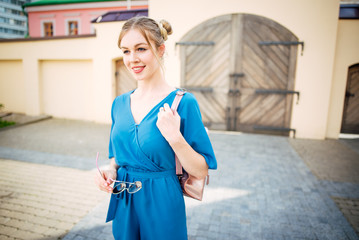 Beautiful woman in blue dress outdoors . Portrait young girl on the street
