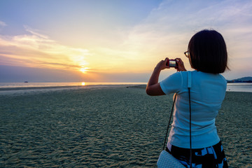 Asian woman tourist taking photo on the beach and beautiful natural landscape of colorful sky and sea during a sunset at Nathon Sunset Viewpoint in Samui island, Surat Thani, Thailand
