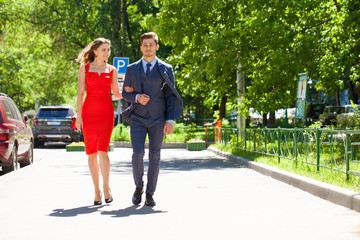 Young couple or european woman and man walking on city street
