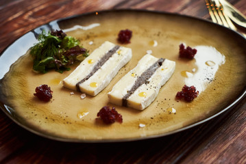 Brie cheese with truffle and jelly barberry. Delicious dish with champignons mushrooms and truffle oil at the restaurant table. Vegetarian delicacy diet food