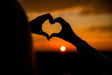 Love.A symbol of love.Heart.Photo at sunset.Hand.Silhouette photo.Lover