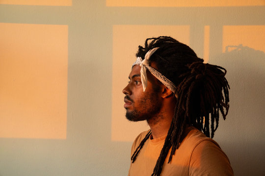 profile of black man with white bandana during golden hour