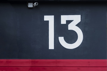 Written number thirteen on the blue concrete wall with camera surveillance
