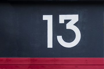 Written number thirteen on the blue red concrete wall