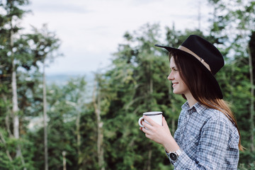girl is drinking coffee in outdoor . Enjoying Nature on top of mountain concept adventure active vacations outdoor hiking sport