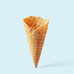 Wafer ice cream cone on a blue background. Minimalistic concept.