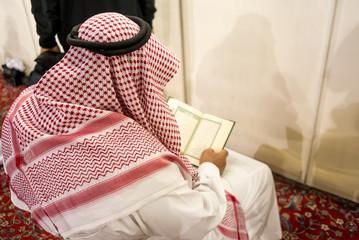 MEDINA, SAUDI ARABIA - APRIL 28 2018: A man in Arabic traditional dress sitting inside Al-Masjid An-Nabawi or Prophet Muhammed Mosque in Medina, Saudi Arabia. Reading the Holy Quran