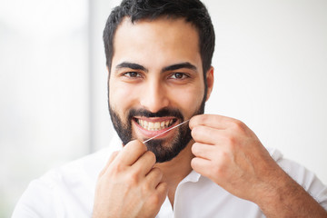 Dental Health. Man With Beautiful Smile Flossing Healthy Teeth. High Resolution Image