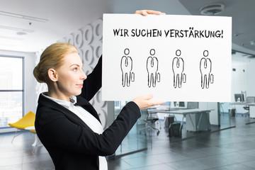 """Geschäftsfrau zeigt Schild mit der Nachricht """"Wir suchen Verstärkung!"""" vor Bürohintergrund"""