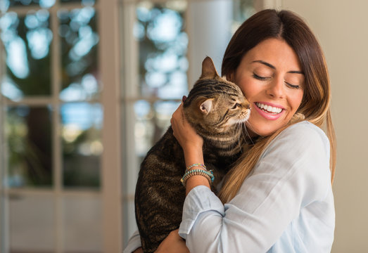 Young beautiful woman smiling and cuddling cat with love at home.