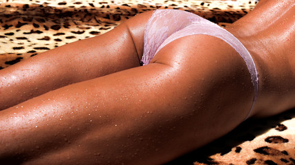 Woman in panties with beautiful butt lies in the sun