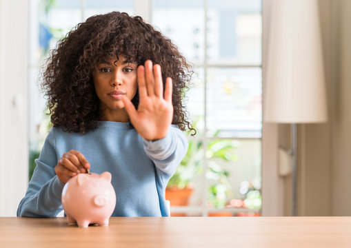 African american woman saves money in piggy bank with open hand doing stop sign with serious and confident expression, defense gesture