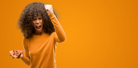 African american woman with a pizza slice annoyed and frustrated shouting with anger, crazy and yelling with raised hand, anger concept