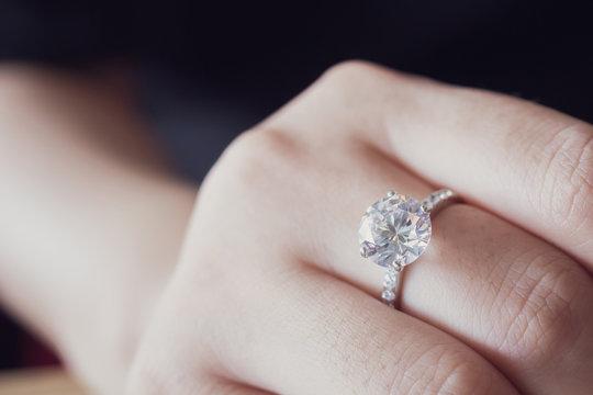 engagement diamond ring on woman finger closeup