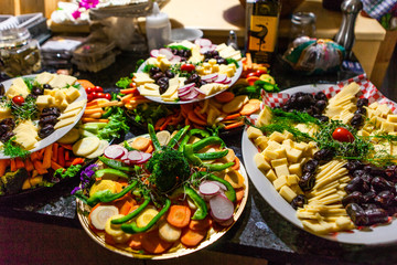 Food platters full of fresh vegetables, cheeses, sprouts and dates