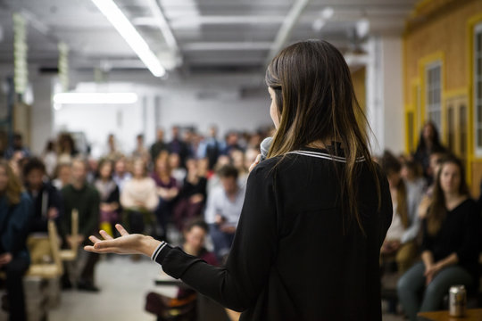 Woman gives a public speech in front of 200 people, in an industrial environment