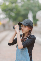 Portrait of asian woman is a professional photographer with mirrorless camera, outdoor portrait, free from copy space.