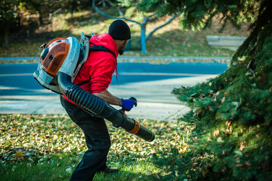 Man holding a leaf blower in the grass, seen from right side