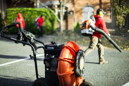 Lawn blower with workers holding leaf blowers in blurred background