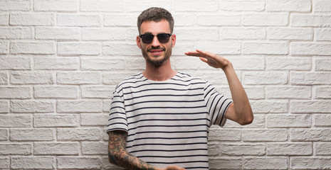 Young adult man wearing sunglasses standing over white brick wall gesturing with hands showing big and large size sign, measure symbol. Smiling looking at the camera. Measuring concept.