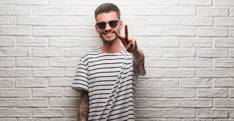 Young adult man wearing sunglasses standing over white brick wall smiling looking to the camera showing fingers doing victory sign. Number two.