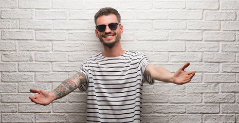 Young adult man wearing sunglasses standing over white brick wall looking at the camera smiling with open arms for hug. Cheerful expression embracing happiness.