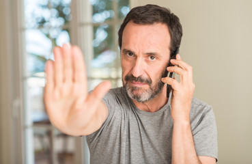 Middle age man using smartphone with open hand doing stop sign with serious and confident expression, defense gesture