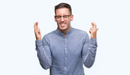 Handsome young elegant man wearing glasses smiling crossing fingers with hope and eyes closed. Luck and superstitious concept.