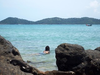 Candid shot from behind rocks of a young slim Asian woman lying in the shallows of a tropical turquoise ocean watching a fishing boat passing by.,