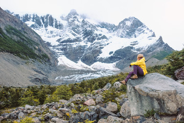A girl in a yellow jacket and tracking clothes is sitting on the rocks in the background of the high snow-capped mountains