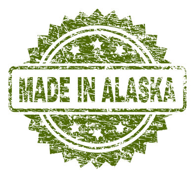 MADE IN ALASKA stamp seal watermark with rubber print style. Green vector rubber print of MADE IN ALASKA title with scratched texture.