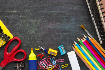 School supplies and stationery on blackboard background.