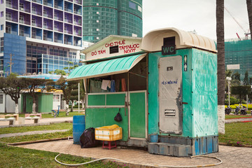 Outdoor toilet and shower plastic cabin at a beach. Ugly cheap WC cabin exterior on a city street. Port-a-potty in an Asian town. Text: Shower and swimming suit for rent. Text on a toilet: Free