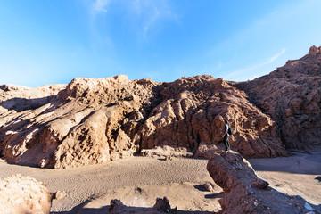 Man stand on a rock of Atacama desert, San Pedro Atacama, Altiplano, Chile
